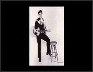 الویس پریسلی گیتار به دست در کنار صندلی