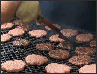 چند همبرگر کبابی که روی باربیکیو در حال پخت هستند