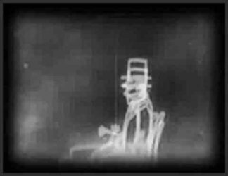 مردی انیمیشنی که روی صندلی نشسته و کلاه دارد