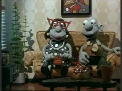 یک مرد و زن خمیری انیمیشنی که روی مبل نشسته ایند و زن بافتنی میکند